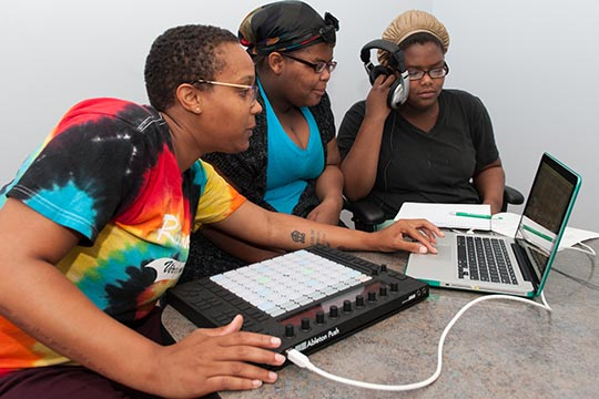 Three women working with a laptop and a sound board.